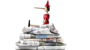 Un Pinocchio assis sur une pile de journaux pour représenté les fausses nouvelles
