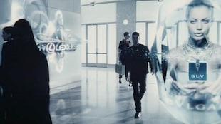 Un homme marche dans une foule d'hologrammes.