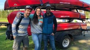 Une femme et deux hommes posent devant une remorque de transport de canots