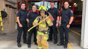 Mireille en armure de pompier pose devant quatre membres de la caserne
