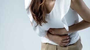 Une femme se tient l'abdomen en raison de douleurs.