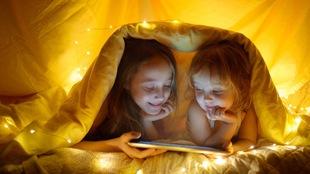 Deux enfants sous une couverture regardent un film sur une tablette.