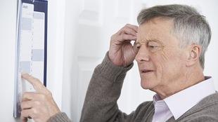 Un homme âgé regarde un calendrier en faisant mine de tenter de se souvenir de quelque chose.