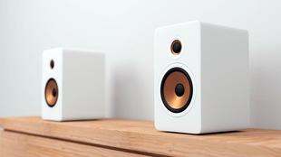 Des haut-parleurs blancs sont sur une table en bois.