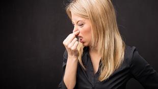 Une femme se bouche le nez.