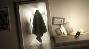 Simulation d'un fantôme recouvert d'un drap blanc dans le couloir d'une maison.