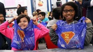 Des enfants montrent fièrement leur sac bleus avec la mention Breakfast2Go.