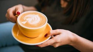 Une femme s'apprête à savourer un café au lait.