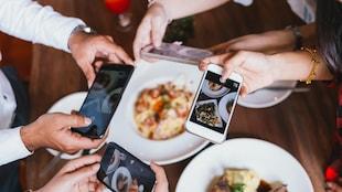 Un groupe d'amis prennent chacun une photo de leur assiette pleine dans un restaurant.