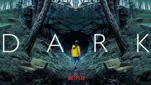 Un homme avec un manteau jaune hésite à entrer dans une cave sous les arbres d'une forêt noire. Le mot DARK est inscrit en lettres majuscules blanches.