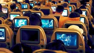 Des passagers d'avion regardent le petit écran individuel devant eux.