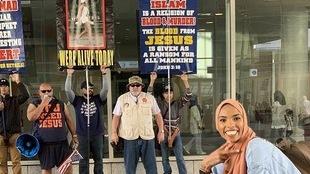 Une jeune femme avec un hijab sourit devant des manifestants chrétiens tenant des pancartes anti-Islam.