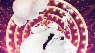 Jennifer Lopez sur un gateau géant avec des ballons blancs, habillée d'une robe de tulle, sur un arrière fond rose et mauve de lumières et de confettis.