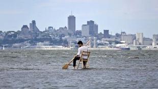 Un homme est assis sur une chaise avec une rame au milieu de l'eau, avec la ville de Québec en arrière-plan.
