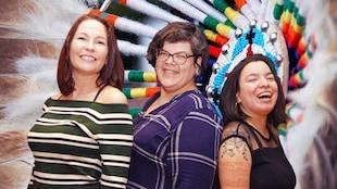 Portrait des trois femmes avec un motif de perlage et de plumes en arrière-plan.