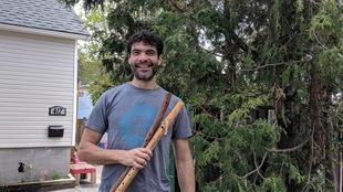 Un homme aux cheveux noirs tenant deux flûtes en bois devant un cèdre.