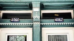 Deux plaques en métal bleues avec des chiffres blancs placées chacune au-dessus d'une porte d'appartement.