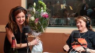 La journaliste sourit en brandissant le bouquet de fleurs de la gagnante.