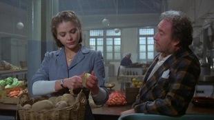 Une femme épluche des pommes de terre alors qu'un homme, accoté sur le comptoir, la regarde travailler.
