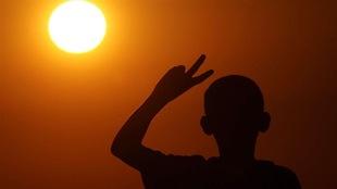 Un jeune garçon fait le signe de la paix (V) avec sa main