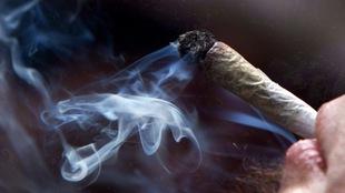 Un jeune homme fume un joint de cannabis.