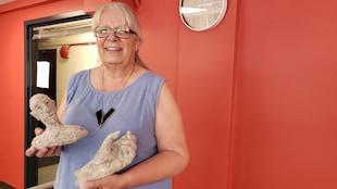 Rosemarie Péloquin, sculptrice avec le textile tient dans les deux mains les sculptures en laine.