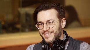 Jean-Sébastien Sauvé souriant au micro du studio 18 de Radio-Canada