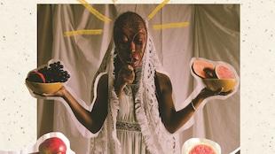 Montage photo représentant une femme habillée de dentelle blanche, un masque africain devant le visage, et qui tient différents fruits dans ses mains.