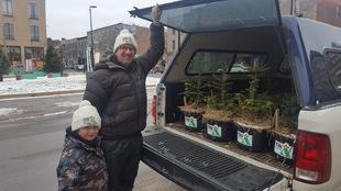 Un père et son fils sourient à la caméra devant une voiture remplie de sapins baumiers.