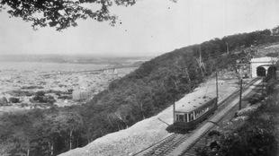 Photo en noir et blanc montrant un tramway au sommet d'une montagne avec la ville de Montréal en contrebas.