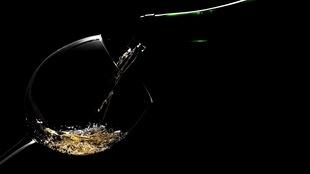 Un verre de vin légèrement éclairé sur fond noir