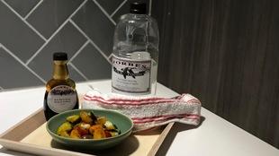 Un plateau avec une bouteille de sirop de bouleau, une bouteille de sève de bouleau et une salade de tomates et de concombres.