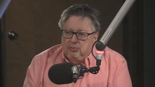 Yves Frenette est assis en studio radio derrière un microphone