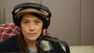 Une femme aux yeux noisettes porte un casque d'écoute et une casquette. Elle est assise dans un studio de radio et fixe la caméra d'un regard calme et sérieux.