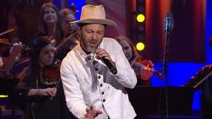Un chanteur sur scène avec un chapeau de paysan.