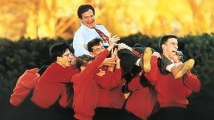 Un homme en chemise et qui rit porté en triomphe par plusieurs jeunes en chandail rouge.