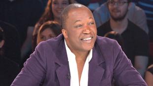 L'homme en veston mauve et chemisier blanc sur le plateau des Enfants de la télé.