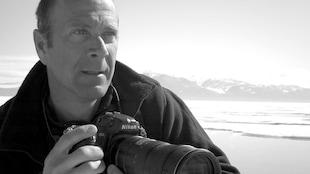 La photo est en noir et blanc. Il tient dans ses mains un appareil photo.