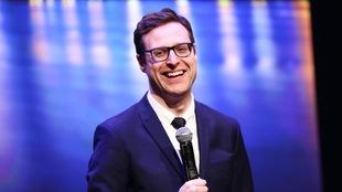 Un jeune homme à lunettes, souriant, un micro à la main