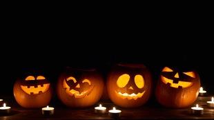 Quatre citrouilles décorées pour l'Halloween sont éclairées par des chandelles dans le noir.