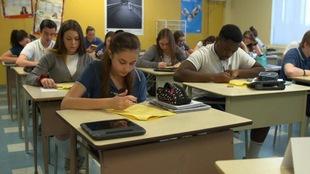 Des élèves du secondaire travaillent à leurs pupitres.