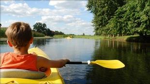 On voit un jeune garçon, de dos, en kayak qui pagaie sur un cours d'eau étroit.
