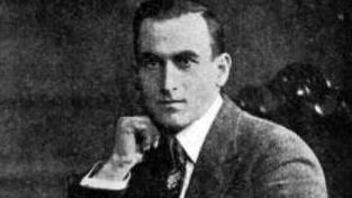 Photo en noir et blanc d'un homme en costume assis et accoudé à un meuble.