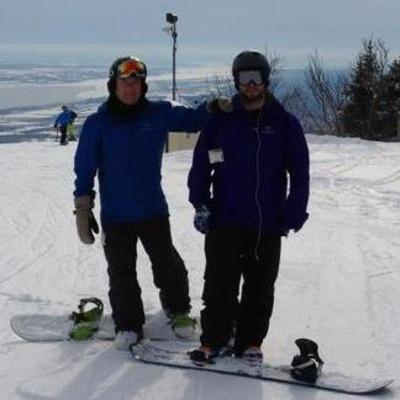 Photo du père et fils faisans du surf des neiges.