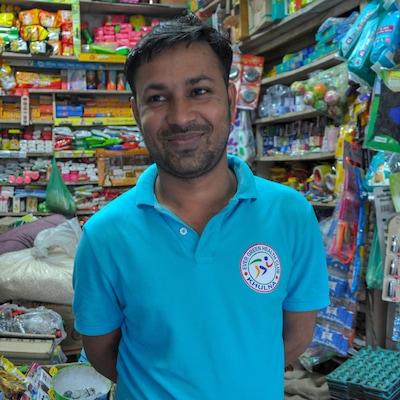Un homme sourit dans un magasin aux étagères bien remplies.