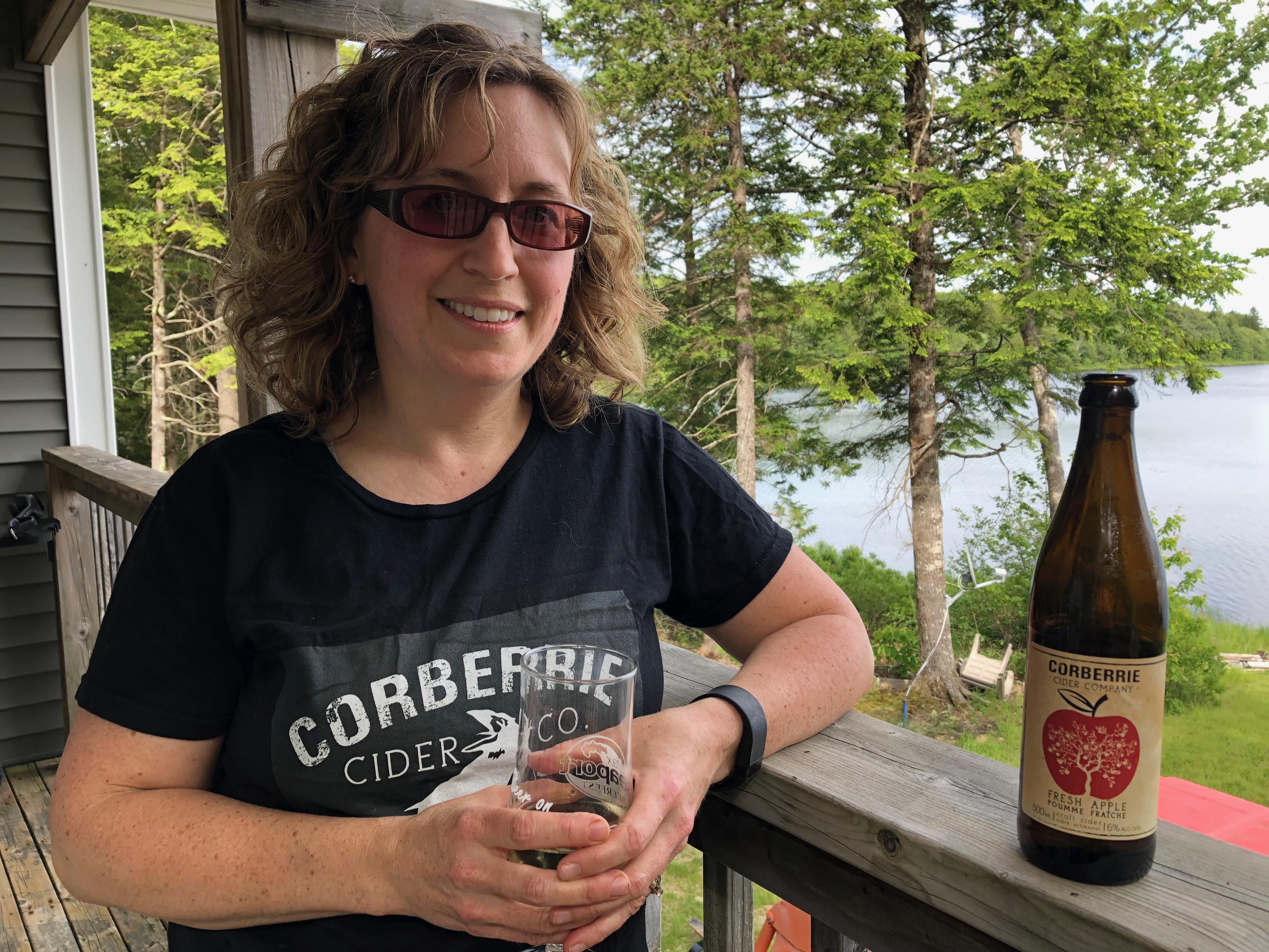 Denise Flynn pose à côté d'une bouteille de cidre Corberrie.