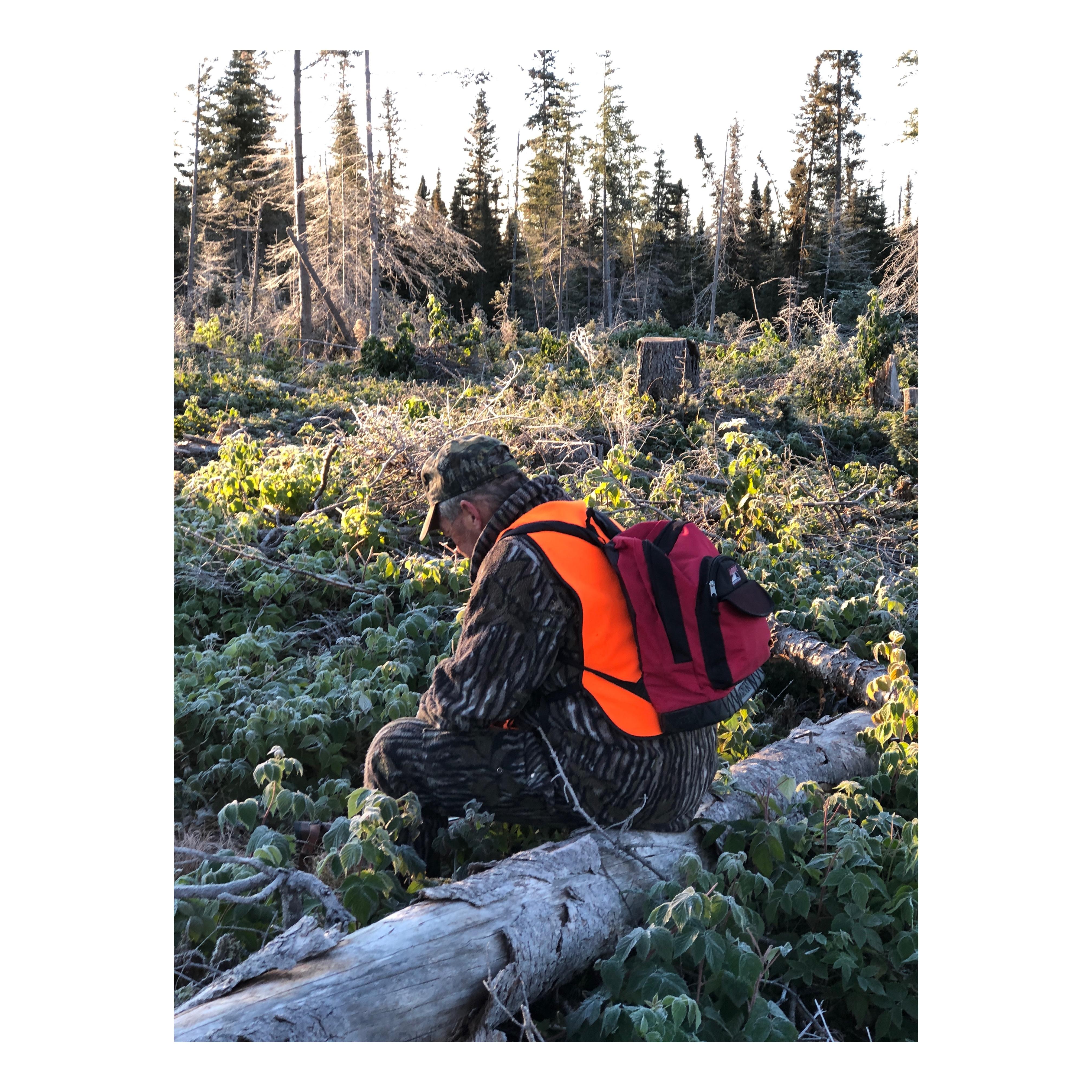 Paul-Aimé Boulay, le père de Stéphanie, prend un moment de repos pendant la chasse. Il est assis sur un tronc dans la forêt.