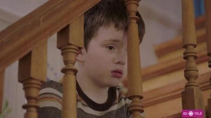 Assis dans l'escalier, le petit Olivier regarde dans le vide à travers les barreaux de la rampe.