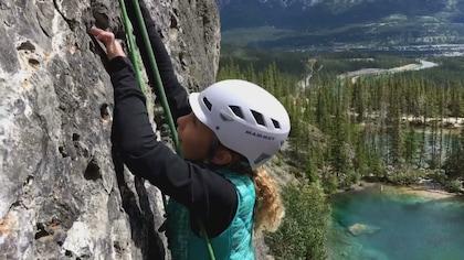Alexa grimpe sur une falaise avec derrière elle la montagne