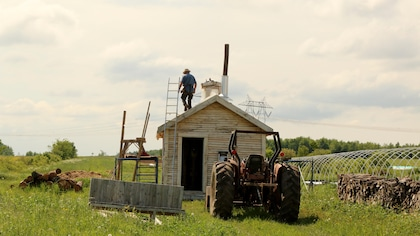 Le tracteur et un homme sur le toit d'une cabane.